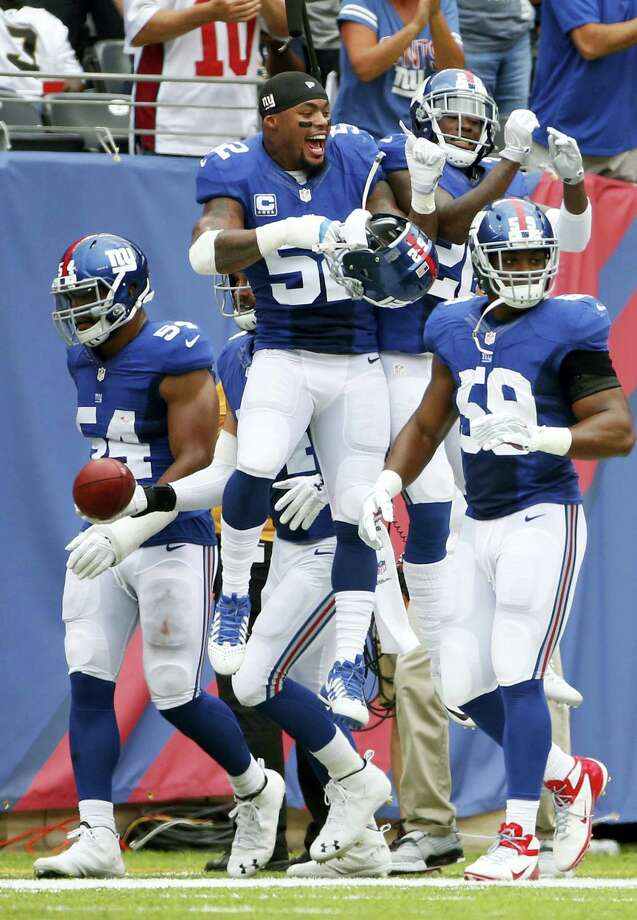 Giants outside linebacker Jonathan Casillas (52) celebrates with teammate Janoris Jenkins and Devon Kennard (59) and Olivier Vernon (54) after Jenkins returned a blocked field goal for a touchdown on Sunday. Photo: Kathy Willens — The Associated Press  / Copyright 2016 The Associated Press. All rights reserved.