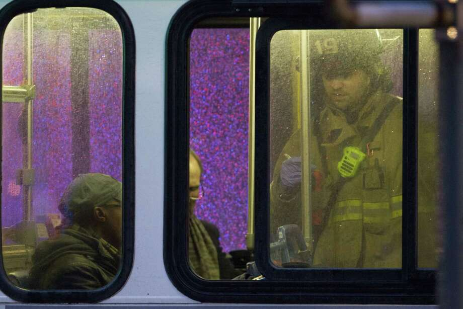 FILE - In this Jan. 12, 2015 file photo, a firefighter attends people on a bus to assess triage needs after people were evacuated from a smoke filled Metro subway tunnel in Washington. Passengers on a smoke-filled subway train in the nation's capital were still asking when help would arrive 27 minutes after the smoke was first reported, District of Columbia officials said Thursday. One woman died and dozens more were sickened when the train filled with smoke Monday afternoon near a busy station in downtown Washington. The cause of the electrical malfunction that led to the smoke remains under investigation.  (AP Photo/Jacquelyn Martin, File) Photo: AP / AP