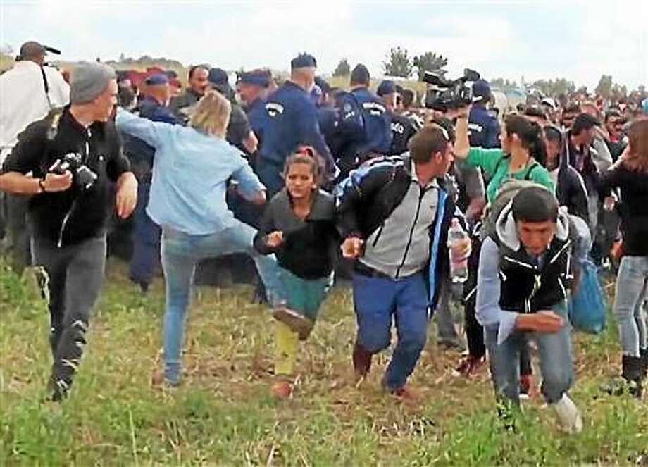 """In this image taken from TV a Hungarian camerawoman, center left in blue, kicks out at a young migrant who had just crossed the border from Serbia  near Roszke Hungary Tuesday Sept. 8, 2015. The camerawoman has been fired after she was caught on video kicking and tripping migrants entering Hungary across the border with Serbia. The N1TV Internet channel said their employee, widely identified in Hungarian media as Petra Laszlo, has been dismissed because she """"behaved unacceptably"""" at a makeshift gathering point where police take migrants immediately after they enter Hungary near the village of Roszke. Photo: Index.Hu. Via AP   / INDEX.Hu Via AP Television"""