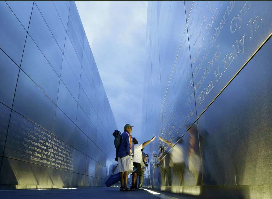 "Jimmie Corley and wife, Rosiland Corley look for the name of a family member on the ""Empty Sky"" memorial to New Jersey's victims of the Sept. 11, 2001 terrorist attacks early Friday, Sept. 11, 2015, in Jersey City, N.J.  Victims' relatives began marking the 14th anniversary of Sept. 11 in a subdued gathering Friday at ground zero, with a moment of silence and somber reading of names. Photo: AP Photo/Mel Evans   / AP"