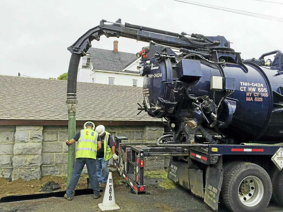 (Ben Lambert/The Register Citizen)  An underground heating oil tank at the Sons of Italy Hall, 34 Center St. in Torrington, which overflowed into the Naugatuck River, prompted a hazmat response in Torrington early Monday morning. Above, a team removes a combination of oil and water from the underground tank on Center Street. Photo: Journal Register Co.