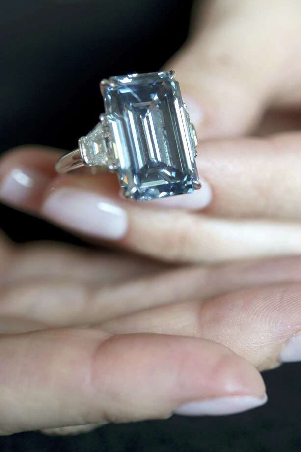 """In this May 12, 2016, file picture, a  Christie's employee holds the """"Oppenheimer Blue"""" diamond of 14.62 carats, which is estimated to be sold between 39 to 46 million US dollars, during a preview at the auction house Christie's, in Geneva, Switzerland. The auction will take place on Wednesday May 18, 2016, in Geneva. Photo: Martial Trezzini/Keystone Via AP,file   / KEYSTONE"""