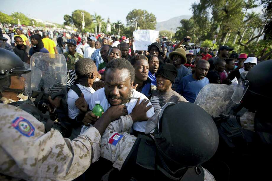 National police officers stop protesters in front of the National Palace during a January protest demanding the resignation of President Michel Martelly in Port-au-Prince, Haiti. Photo: File Photo  / AP