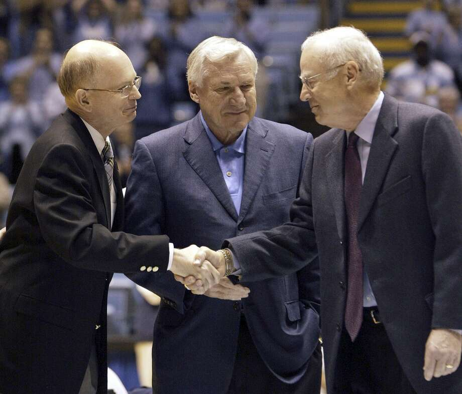 In this Feb. 21, 2004 file photo, former North Carolina coaches Dean Smith, center, and Bill Guthridge, right, shake hands with chancellor James Moeser as they are honored before the start of a game in Chapel Hill, N.C. Photo: Grant Halverson — The Associated Press  / AP
