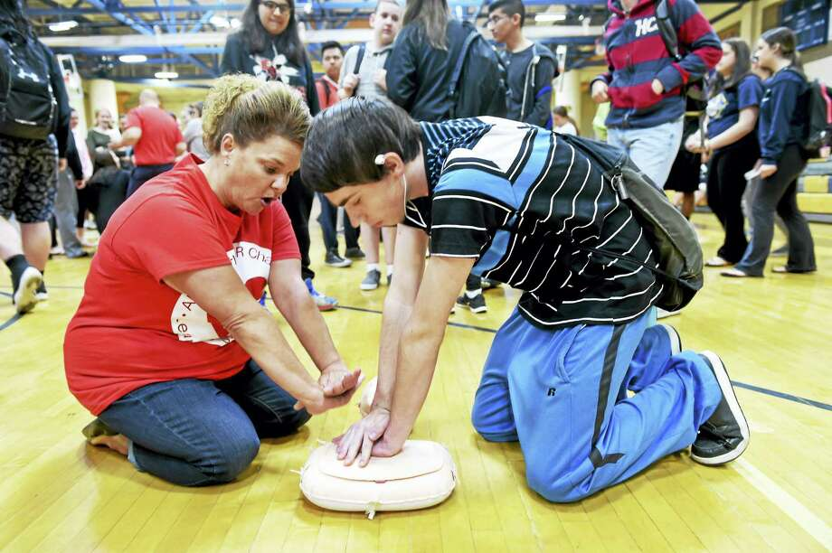Gina Fronte, an American Medical Response paramedic and Tuttle Elementary School secretary, left, instructs East Haven High School tenth-grader Nick Wilson, 16, in hands-only CPR Wednesday in the East Haven High School gynmasium. Photo: Peter Hvizdak — New Haven Register  / ©2016 Peter Hvizdak