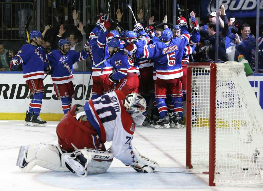 The Rangers celebrate the game-winning overtime goal by Derek Stepan against the Washington Capitals in Game 7 as Capitals goalie Braden Holtby looks at the puck in the net. The Rangers won 2-1 to take the series 4-3. Photo: Kathy Willens  — The Associated Press  / AP