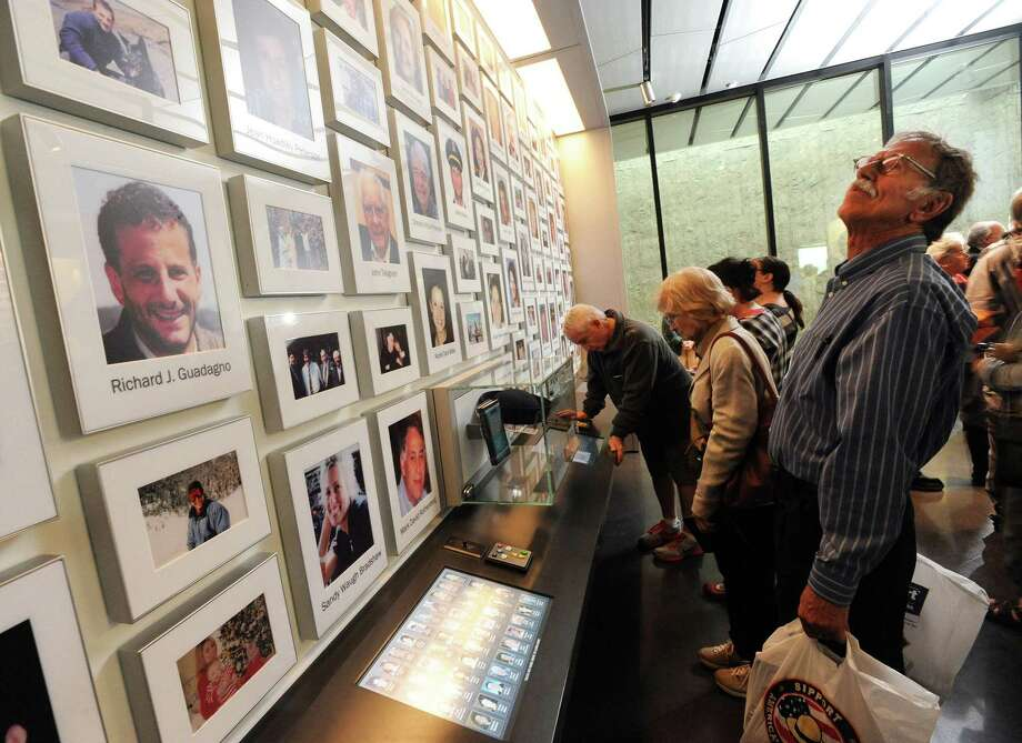 Jan Duncan and her fiance Rege Windisch of Freedom, Pa., look over the victims' photo display at the new Flight 93 National Memorial Visitor Center in Shanksville, Pa., Thursday. Photo: John Rucosky — The Tribune-Democrat Via AP  / The Tribune-Democrat