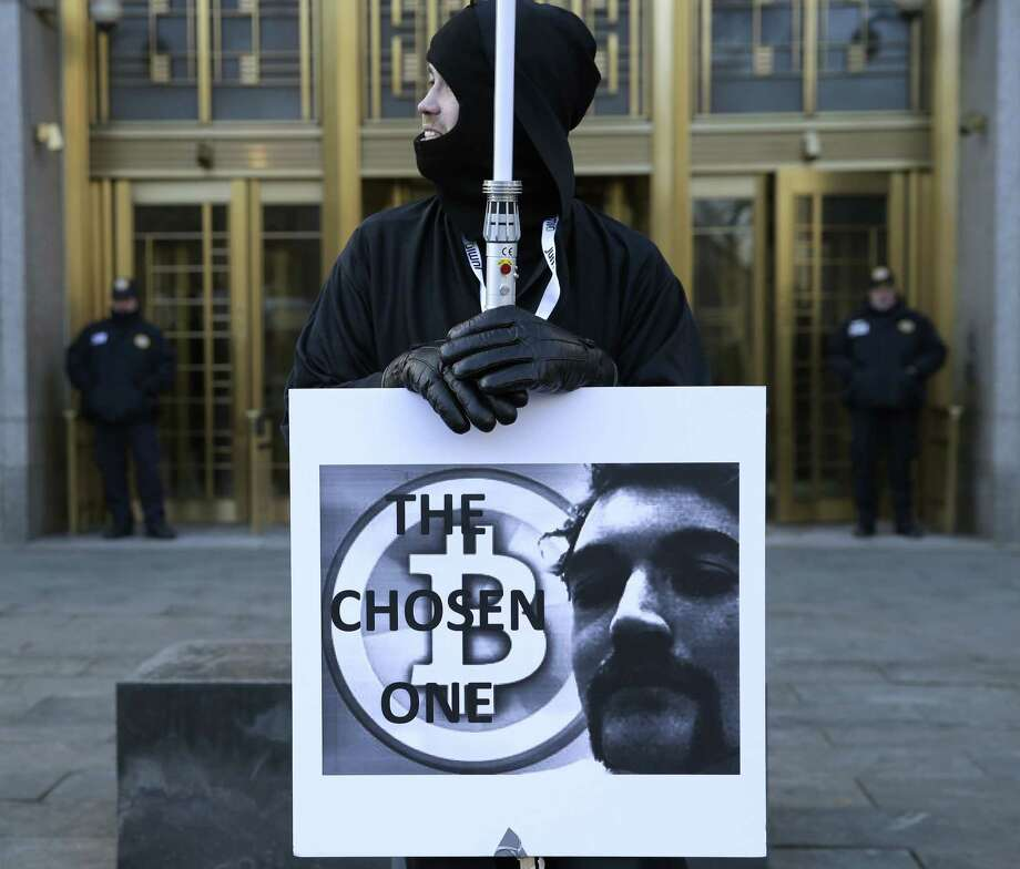 Supporters of Ross William Ulbricht hold signs during the jury selection for his trial outside of federal court in New York, Tuesday, Jan. 13, 2015. Murder-for-hire allegations are central to Ulbrichtt's trial. He is charged with running an online black market where drugs were sold as easily as books and electronics. (AP Photo/Seth Wenig) Photo: AP / AP