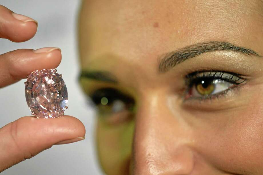In this Sept. 25, 2013 picture a Sotheby's employee shows The Pink Star diamond weighing 59.6 carat, during a preview at Sotheby's, in Geneva, Switzerland. Southeby's on Tuesday, May 17, 2016 is putting up a pearl-shaped pink diamond for auction. Photo: AP Photo/Keystone,Martial Trezzini, File  / KEYSTONE