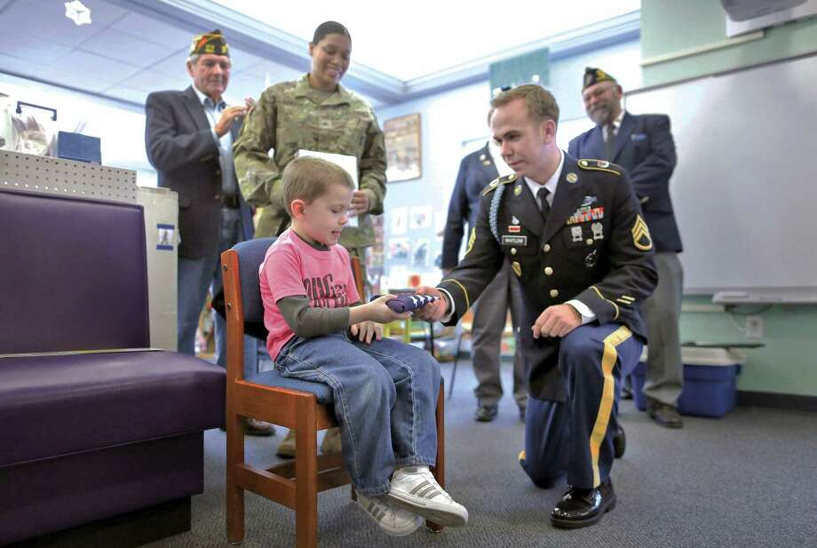 In a Friday, Dec. 11, photo, 4-year-old Logan Barritt receives a small American flag from Staff Sgt.Jordan Whitlow, of the Army recruiting office in Janesville, Wisc., during a thank you ceremony for Logan's efforts in raising more than $1,200 for holiday care packages to soldiers stationed overseas at the Young Women's Christian Association. Logan will be one of House Speaker Paul Ryan's guests for President Barack Obama's final State of the Union address. Photo: Anthony Wahl/The Janesville Gazette Via AP   / The Janesville Gazette