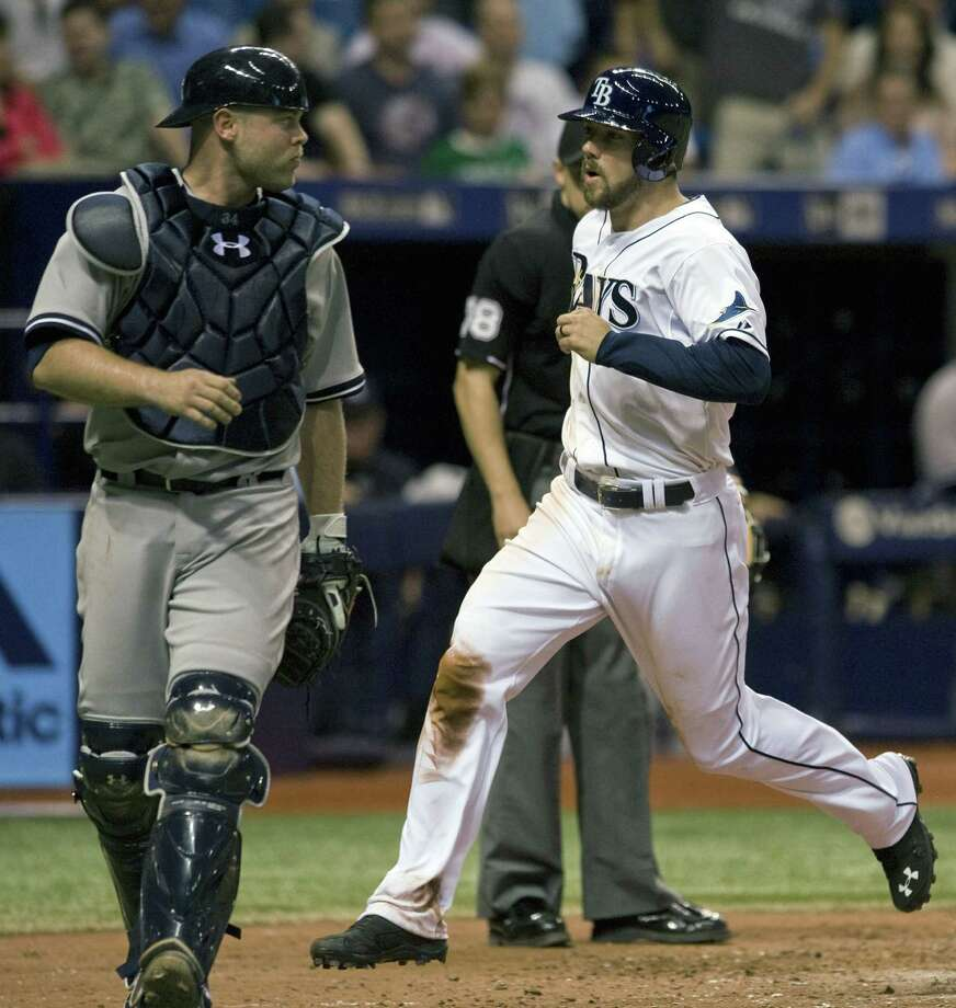 The Rays' Steve Souza Jr. scores past  New York Yankees catcher Brian McCann, left, on a wild pitch in the eighth inning of Tuesday's game. Photo: Steve Nesius — The Associated Press  / FR69810 AP