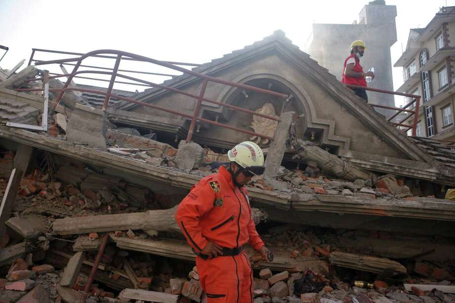 A Mexican rescue worker stands at the site of a building that collapsed in an earthquake in Kathmandu, Nepal on May 12, 2015. A major earthquake has hit Nepal near the Chinese border between the capital of Kathmandu and Mount Everest less than three weeks after the country was devastated by a prior quake. Photo: AP Photo/Niranjan Shrestha  / AP