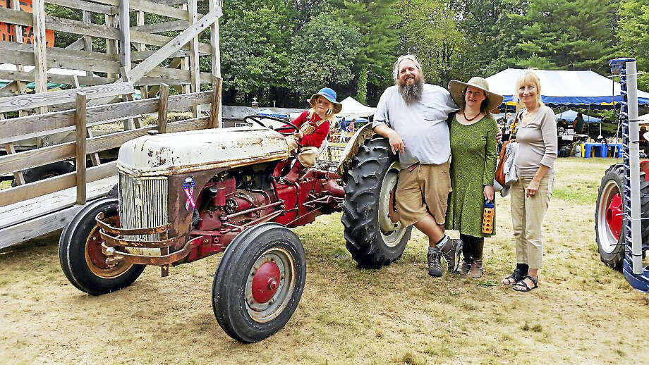 N.F. Ambery photo Noah Alvey, 5, tested out a tractor while supervised by his parents Chris and Amy Alvey of New Hartford and Jean Gaylord of Torrington at the Sunday fair. Photo: Journal Register Co.