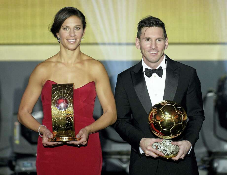 Carli Lloyd, left, and Lionel Messi pose with their trophies after winning the FIFA soccer player of the year awards on Monday. Photo: Walter Bieri — The Associated Press  / KEYSTONE