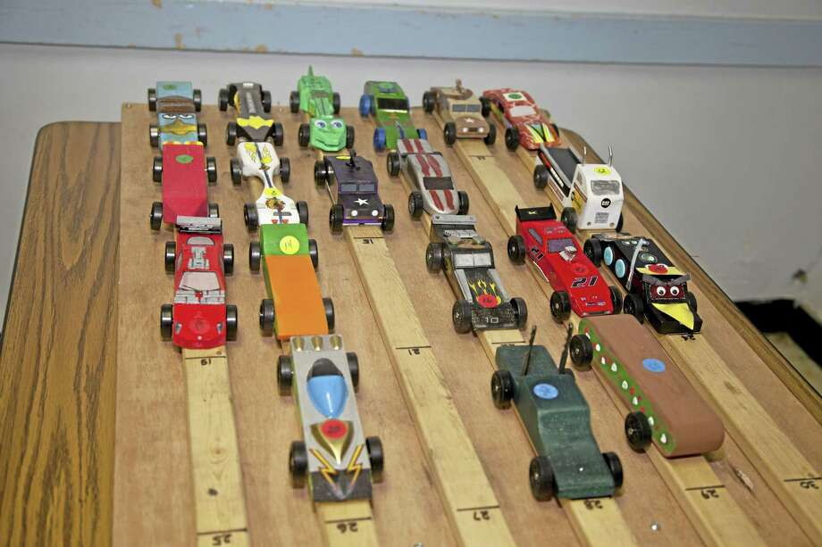 A set of Pinewood Derby cars line up on the inclined track during a recent derby. Photo: DFM File Photo