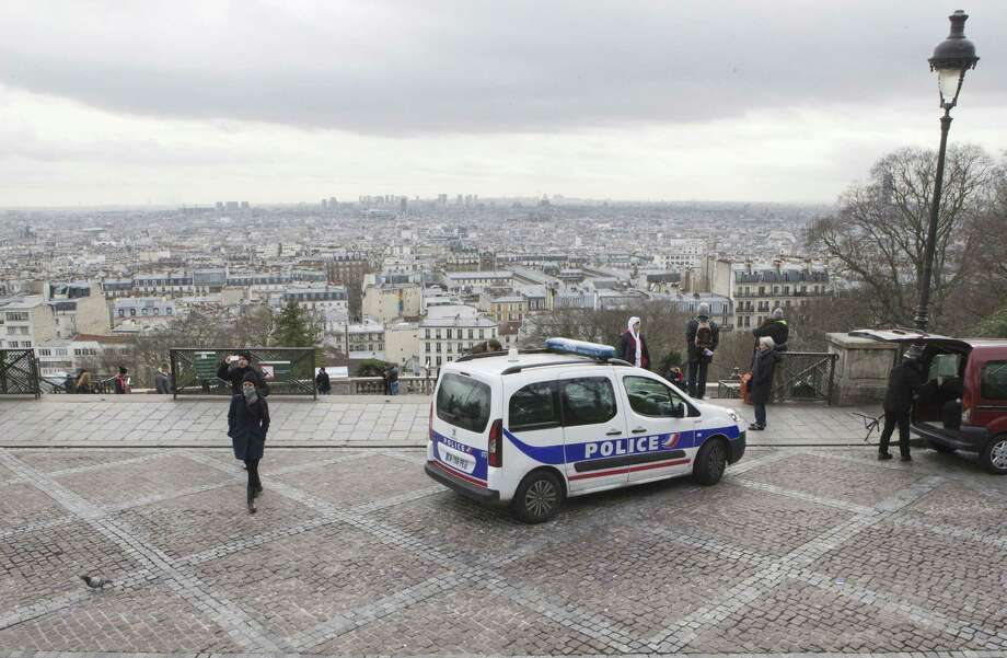 French police car parks outside the Sacre Coeur basilica at Montmartre district, in Paris,, Monday, Jan. 12, 2015. France on Monday ordered 10,000 troops into the streets to protect sensitive sites after three days of bloodshed and terror, amid the hunt for accomplices to the attacks that left 17 people and the three gunmen dead. (AP Photo/Jacques Brinon) Photo: AP / AP