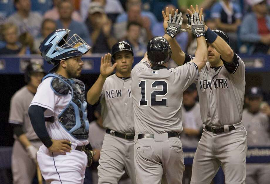 Rays catcher Rene Rivera, left, stands to the side as Yankees' Carlos Beltran, Chase Headley (12) and Mark Teixeira, celebrate Headley's three-run homer on Monday. Photo: Steve Nesius — The Associated Press  / FR69810 AP