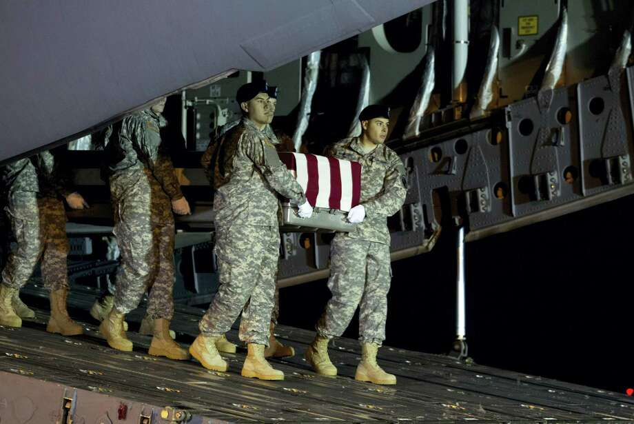 An Army team carries the transfer case containing the remains of Army Staff Sgt. Matthew Q. McClintock of Bernalillo, New Mexico, upon arrival at Dover Air Force Base, Delaware, on Friday. The Department of Defense announced the death of McClintock, who was supporting Operation Freedom's Sentinel in Afghanistan. Photo: JOSE LUIS MAGANA — ASSOCIATED PRESS  / FR159526 AP