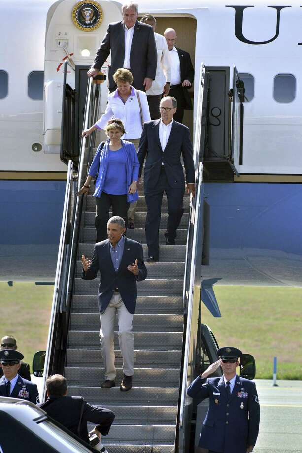 President Barack Obama descends the stairs ftp, Air Force One at Logan Airport in Boston on Labor Day. Following in order are American Federation of Teachers President Randi Weingarten, Labor Secretary Tom Perez, Service Employees International Union President Mary Kay Henry, United Association General President Bill Hite, and partially obscured United Farm Workers President Arturo Rodriguez. Obama was in Boston where he announced an executive order requiring federal contractors to give their workers paid sick leave. Photo: AP Photo  / FR25426 AP