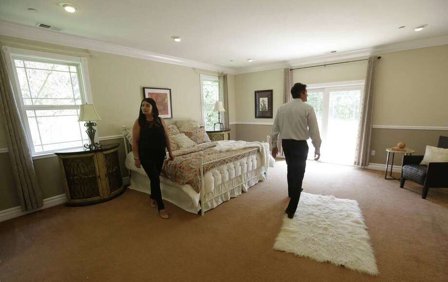 In this May 6, 2015 photo, realtor Stephan Marshall, right, walks with potential buyer Sasha Martinez at a home for sale on Perez Drive in Pacifica, Calif. Photo: AP Photo/Jeff Chiu  / AP