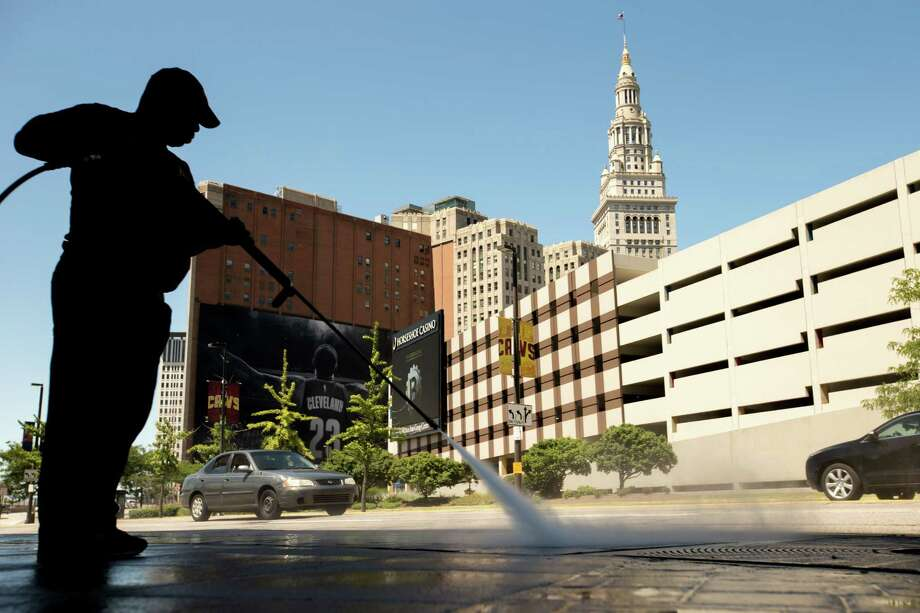 A worker cleans the sidewalk in front of the Quicken Loans Arena in Cleveland on Aug. 5, 2015 before Thursday's first Republican presidential debate being held at the arena. Photo: AP Photo/Andrew Harnik  / AP