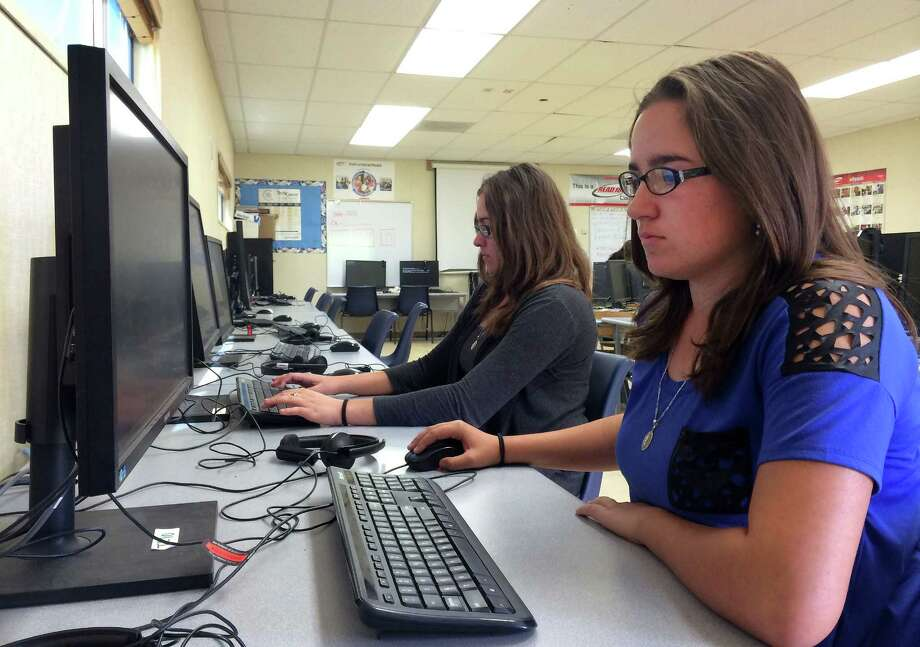 In this April 30, 2015 photo, Leticia Fonseca, 16, left, and her twin sister, Sylvia Fonseca, right, work in the computer lab at Cuyama Valley High School after taking the new Common Core-aligned standardized tests in New Cuyama, Calif. Photo: AP Photo/Christine Armario  / AP