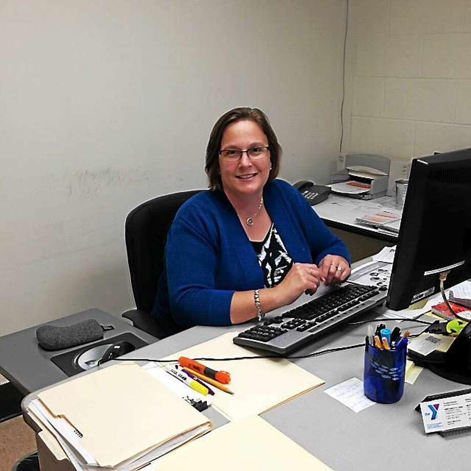 Development Director Yvonne Johnson sits behind her new desk at the Torrington YMCA. Photo: Amanda Webster — The Register Citizen