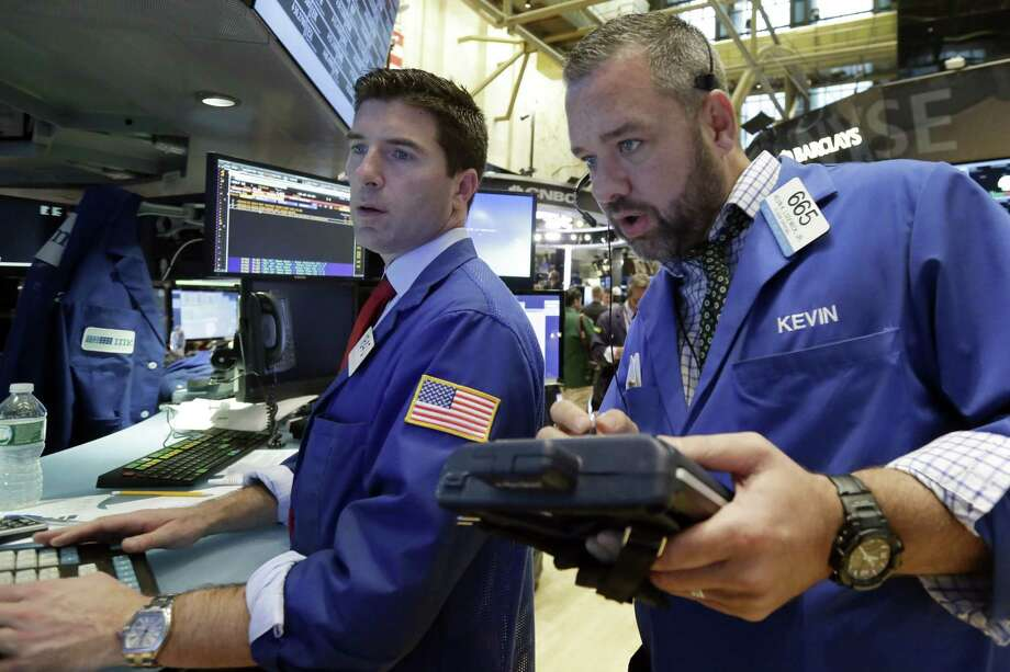 Specialist Thomas McArdle, left, and trader Kevin Lodewick work on the floor of the New York Stock Exchange. Photo: AP Photo/Richard Drew  / AP
