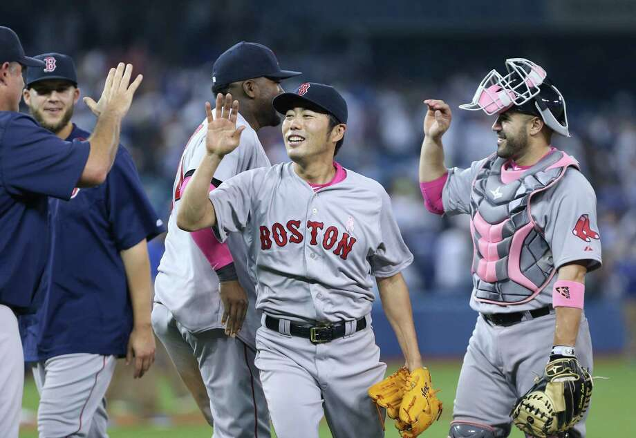 Closer Koji Uehara high-fives with teammates after the Red Sox beat the Blue Jays on Sunday in Toronto. Photo: Peter Power — The Canadian Press  / CP