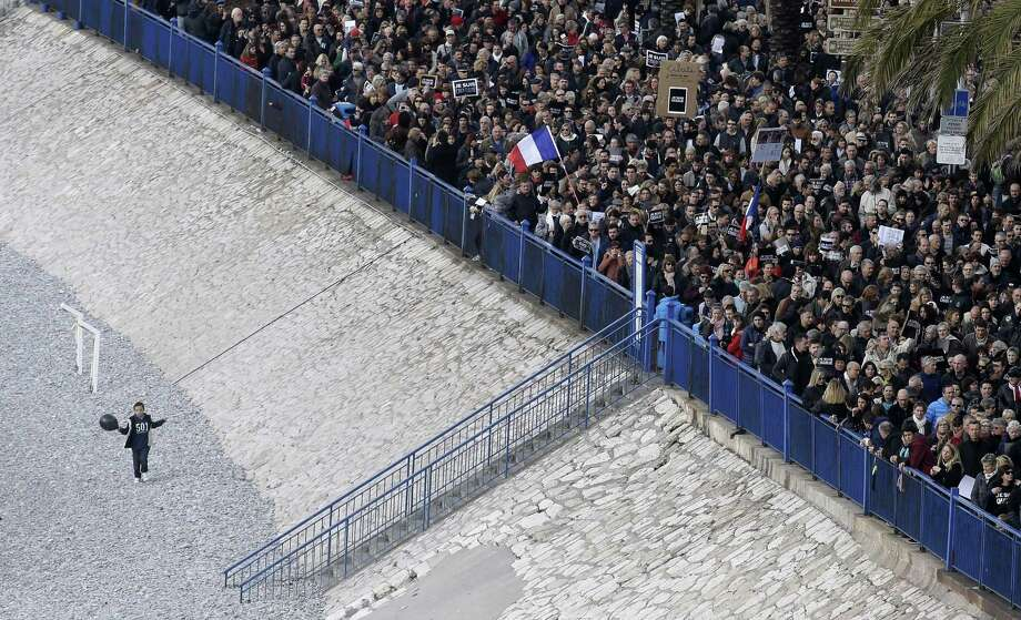 A child holding a ball and standing on the beach of Nice, looks at a silent march for victims of the shooting at the satirical newspaper Charlie Hebdo, Saturday in Nice, southeastern France. Ten journalists and two policemen were killed earlier this week in a terrorist attack at the Charlie Hebdo headquarters in Paris. Photo: (AP Photo/Lionel Cironneau) / AP