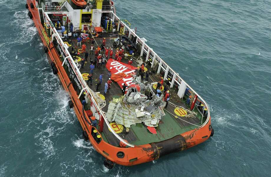 Portion of the tail of AirAsia Flight 8501 is seen on the deck of rescue ship after it was recovered from the sea floor on the Java Sea, Saturday, Jan. 10, 2015. Investigators searching for the crashed plane's black boxes lifted the tail portion of the jet out of the Java Sea on Saturday, two weeks after it went down, killing all 162 people on board. (AP Photo/Prasetyo Utomo, Pool) Photo: AP / POOL Antara