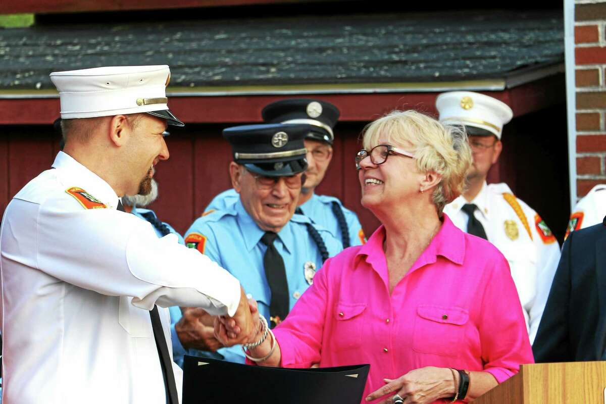 Norfolk First Selectman Susan M. Dyer, who also read a General Assembly citation marking the event, congratulates Norfolk Volunteer Fire Chief Matthew Ludwig.