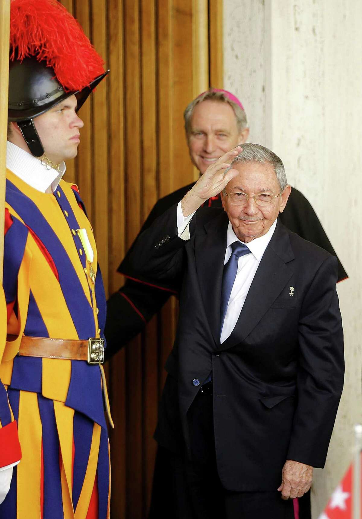 """Cuban President Raul Castro waves as a Swiss Guard, left, and Archbishop George Gaenswein stand by him, prior to meeting Pope Francis, at the Vatican, Sunday, May 10, 2015. Cuban President Raul Castro received a warm welcome at the Vatican Sunday from Pope Francis, who played a key role in the breakthrough between Washington and Havana aimed at restoring U.S.-Cuban diplomatic ties, and later lavished praise on the pontiff for his """"wisdom."""" (Fabio Frustaci/ANSA via AP)"""