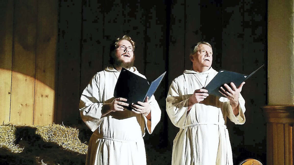 "N.F. Ambery photo Soloists John Eggering and Brian Tassinari, dressed as Medieval monks, performed ""O Come, O Come, Emmanuel"" at the 26th annual Boar's Head Festival."