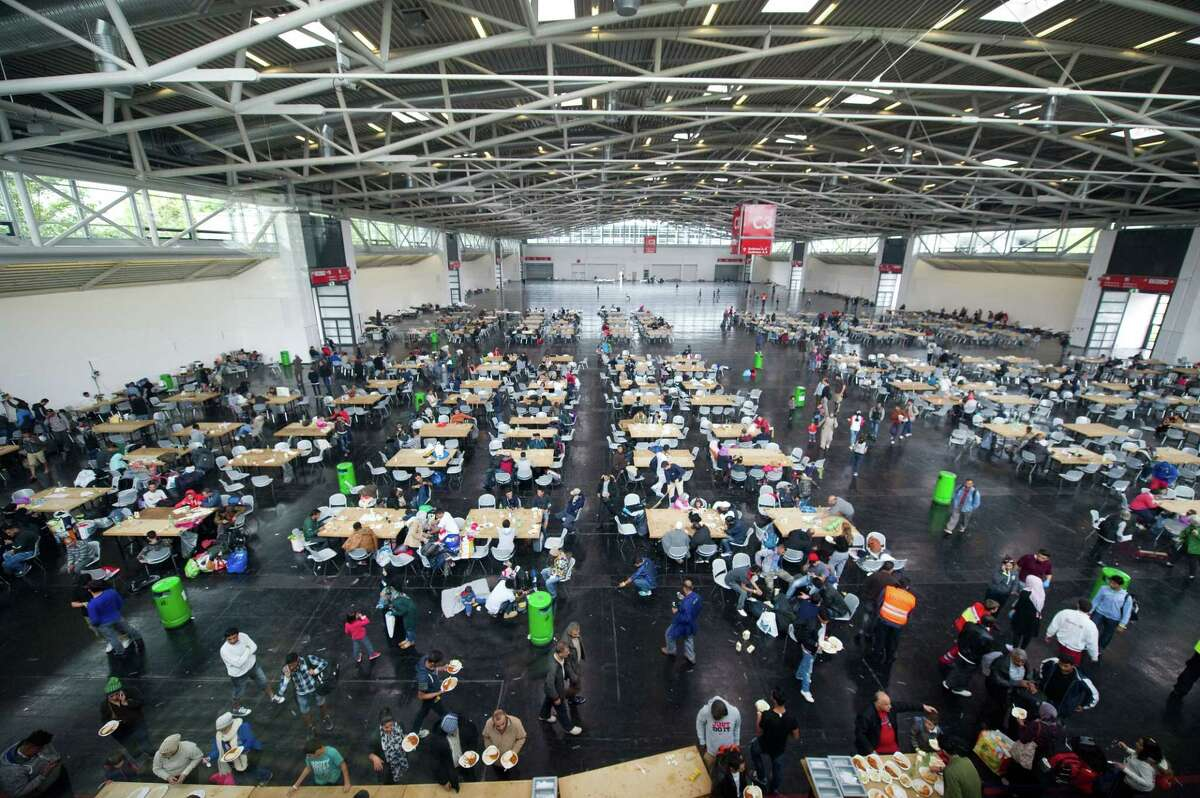 Refugees rest inside the refugee reception facility at the trade fair in Munich, Germany, Monday, Sept. 7, 2015.