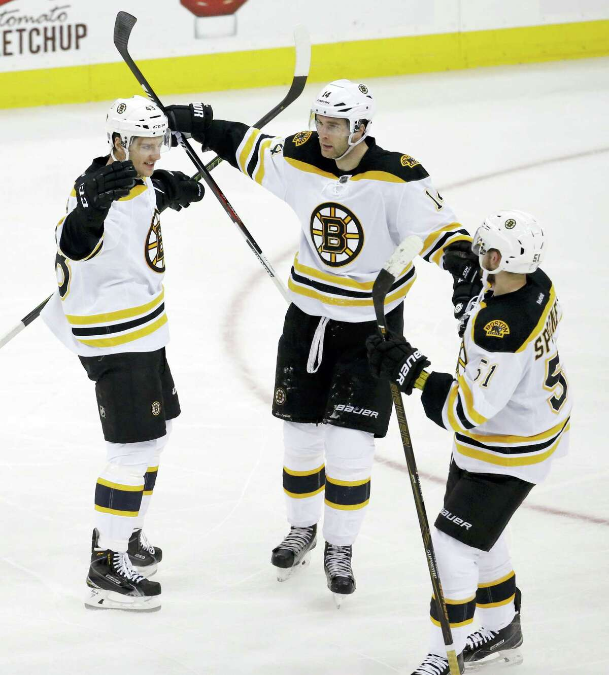 Boston Bruins' Colin Miller, left, Brett Connolly, center, and Ryan Spooner celebrate a goal by Miller against the New Jersey Devils during the third period of an NHL hockey game, Friday, Jan. 8, 2016, in Newark, N.J. The Bruins won 4-1. (AP Photo/Julio Cortez)