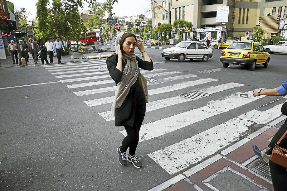 In this file photo, an Iranian woman adjusts her hijab while crossing a street in downtown Tehran, Iran. Photo: Vahid Salemi/AP