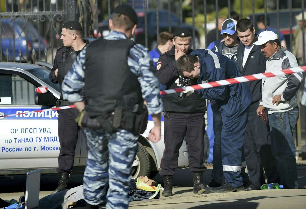 Police investigators work on the site of a brawl at the Khovanskoye cemetery in in Moscow, Russia, Saturday, May 14, 2016. Moscow police say a brawl at the cemetery involving up to 200 people has left two people dead and 10 wounded. Russian news reports cited police as saying the brawl was believed to have been about control over providing burial services at the sprawling Khovanskoye cemetery in southwest Moscow.