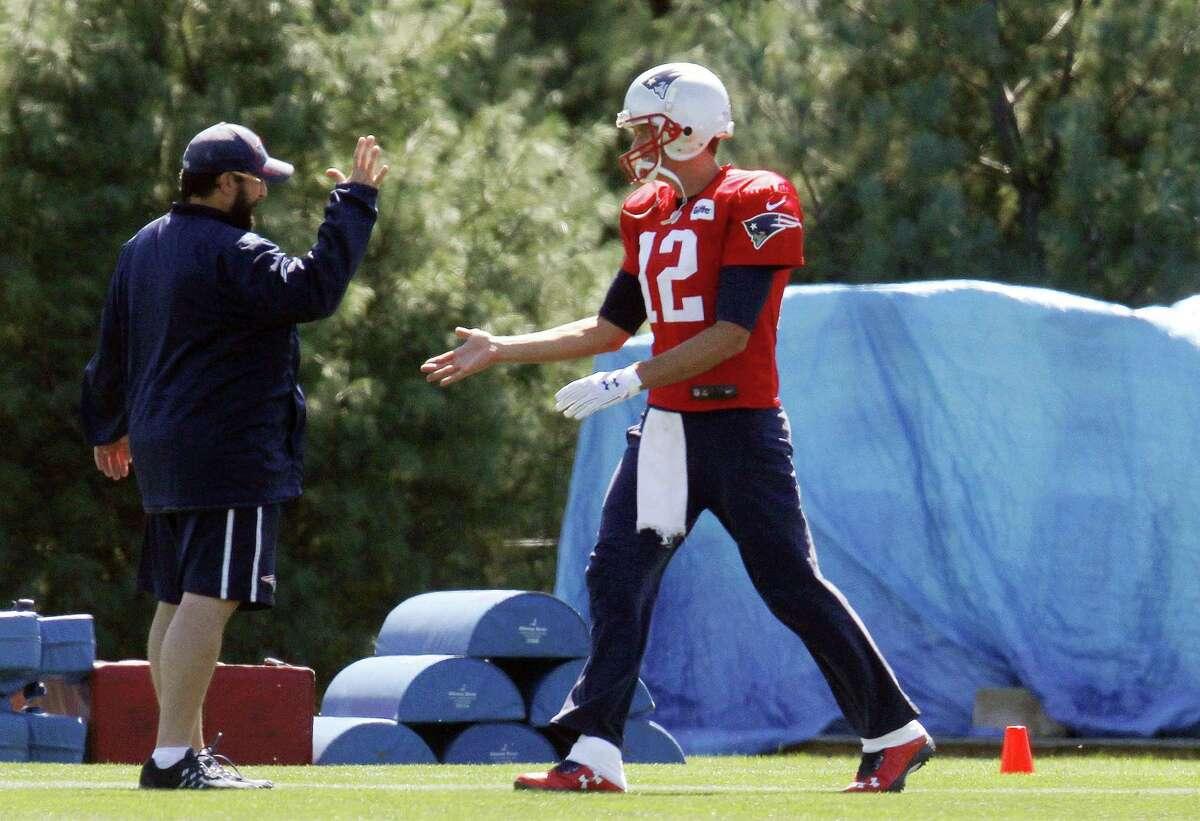Patriots quarterback Tom Brady (12) greets defensive coordinator Matt Patricia, left, at the start of practice on Saturday.