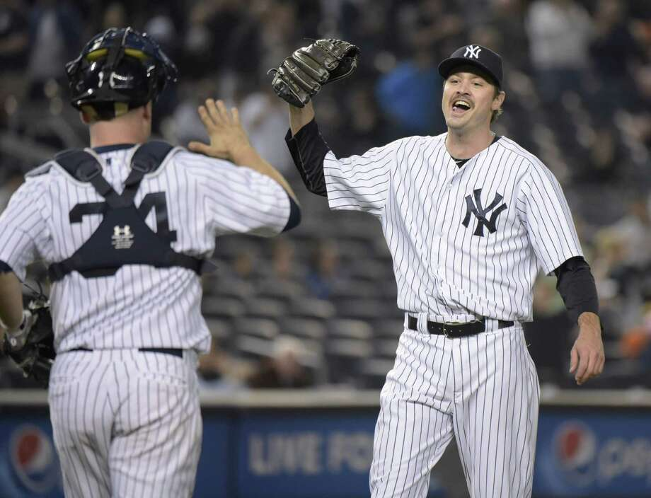 New York Yankees closer Andrew Miller, right, celebrates with catcher Brian McCann after a 5-4 win over the Baltimore Orioles on Friday night at Yankee Stadium in the Bronx. Photo: Bill Kostroun — The Associated Press  / FR51951 AP