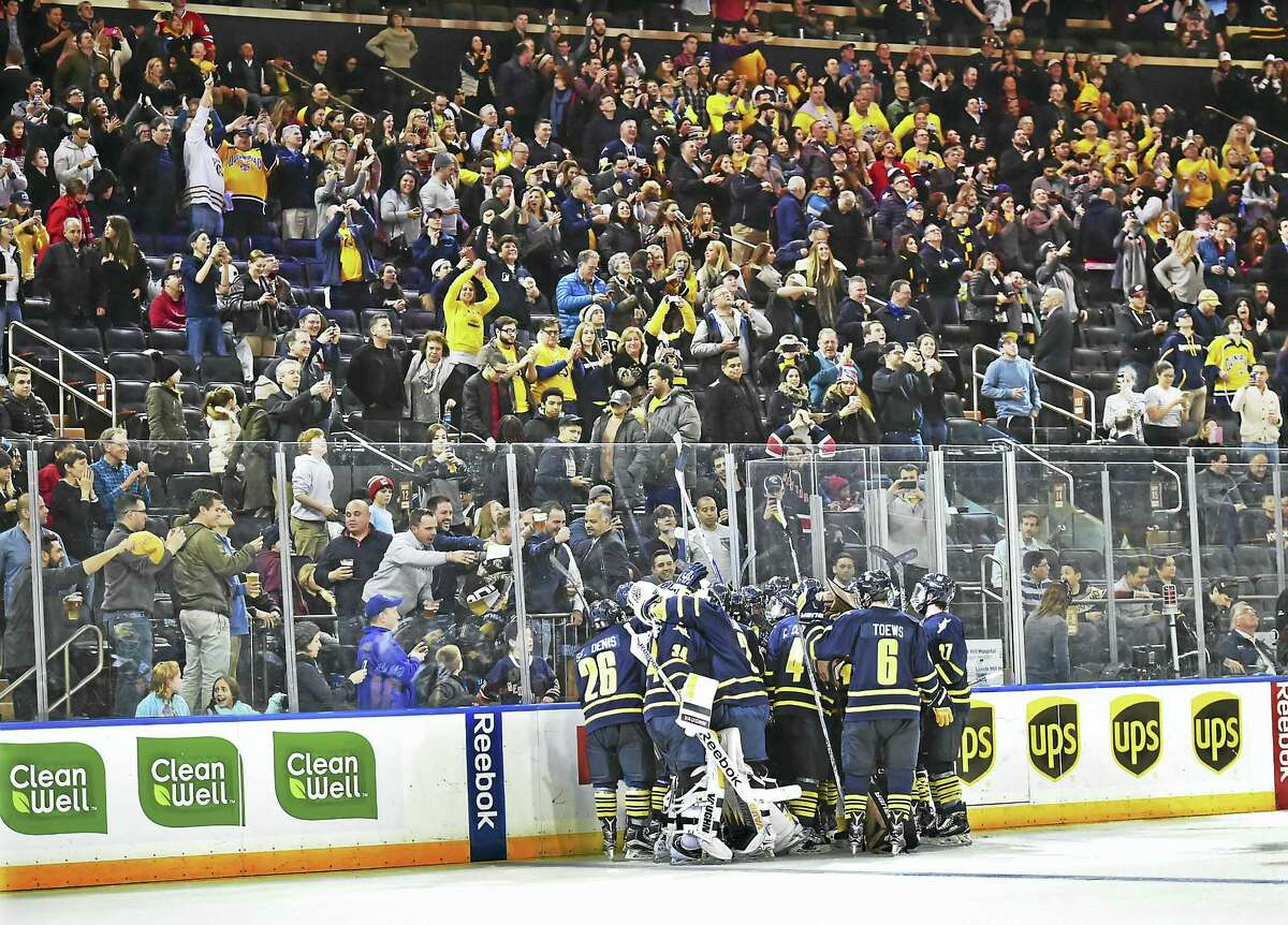 Members of the Quinnipiac hockey team celebrate Derek Smith's overtime goal that gave the Bobcats a 5-4 win over Harvard at the Madison Square Garden in New York on Saturday.
