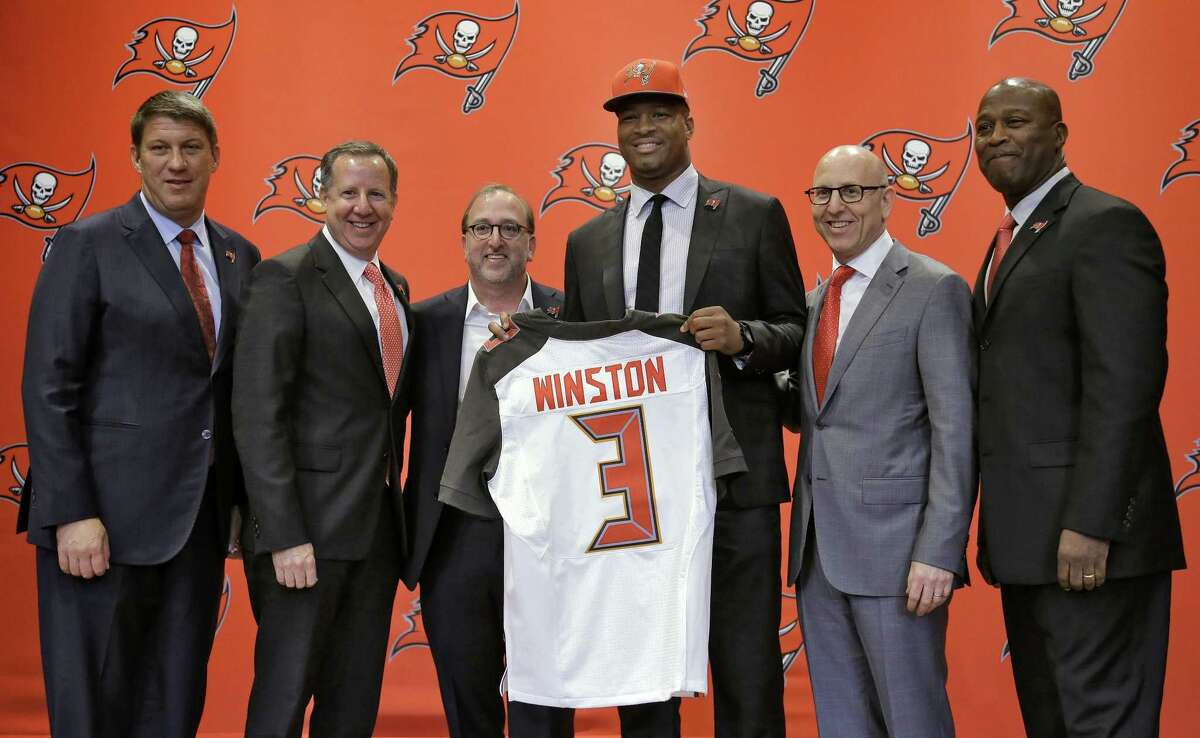 Tampa Bay Buccaneers quarterback Jameis Winston, center, holds up his jersey as he stands with, from left, general manager Jason Licht, co-chairmen Bryan Glazer, Edward Glazer and Joel Glazer, and head coach Lovie Smith, during a news conference on May 1 in Tampa, Fla.