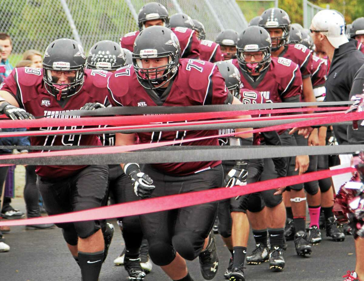 Marianne Killackey - Special to Register Citizen file photo Torrington's Ben Bonvicini, center, leads the Red Raiders to the field during a game this season.