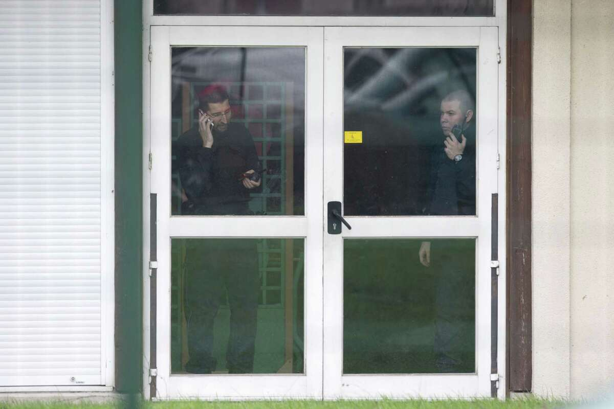 Police officers communicate inside a school of Dammartin-en-Goele, northeast of Paris, Friday Jan. 9, 2015. Brothers suspected in a newspaper terror attack were cornered with a hostage inside a printing house on Friday, after they hijacked a car and police followed them to a village near Paris' main airport. (AP Photo/Peter Dejong)