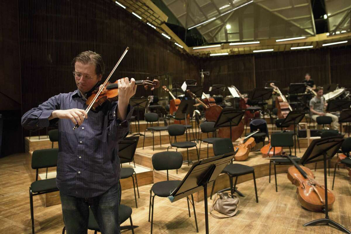 In this May 3, 2015 photo, David Radzynski an American-Israeli concertmaster of the Israel Philharmonic Orchestra, plays during a rehearsal in Tel Aviv concert hall. Radzynski is still getting used to his first job out of college as the new concertmaster of the Israel Philharmonic Orchestra - and to being one of the youngest violinists to lead a major world orchestra today.
