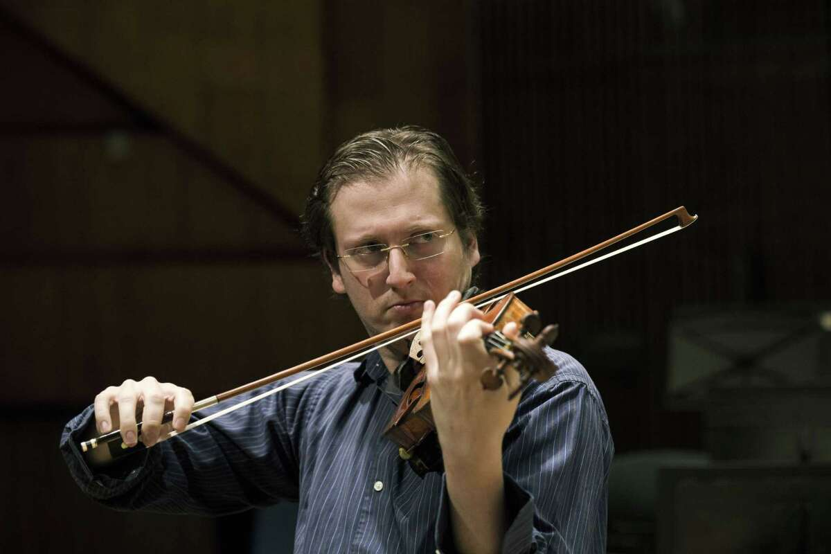 David Radzynski an American-Israeli concertmaster of the Israel Philharmonic Orchestra, plays during a rehearsal in Tel Aviv concert hall.