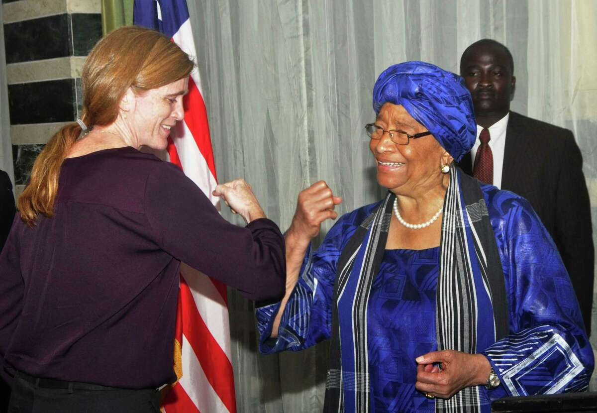 In this Oct. 28, 2014 photo, Liberia President Ellen Johnson Sirleaf, right, gives American ambassador to the United Nations Samantha Power, left, what is know as the 'Ebola hand shake' during a press conference in the city of Monrovia, Liberia. Liberia is now free of Ebola after going 42 days - twice the maximum incubation period for the deadly disease - without any new cases,