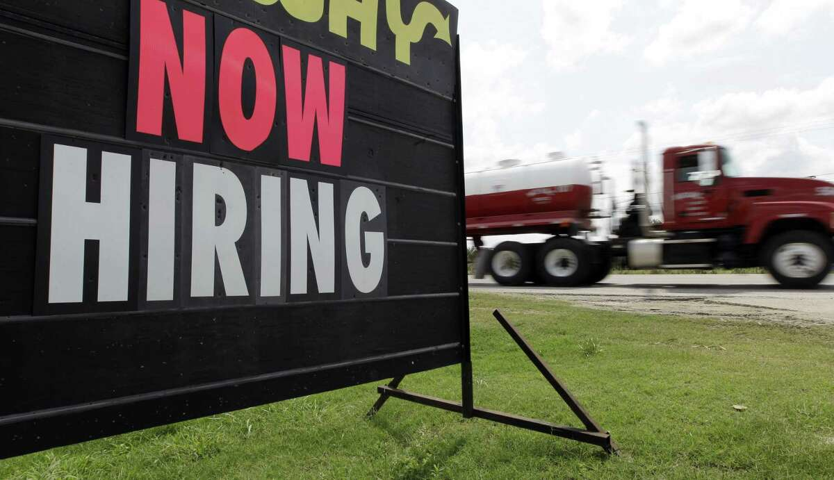 """FILE - In this May 9, 2012 file photo, an oil truck passes a """"now hiring"""" sign in Kennedy, Texas. With the Federal Reserve edging into the spotlight, the Friday, Sept. 4, 2015 jobs report could trigger changes in Americans' financial lives."""