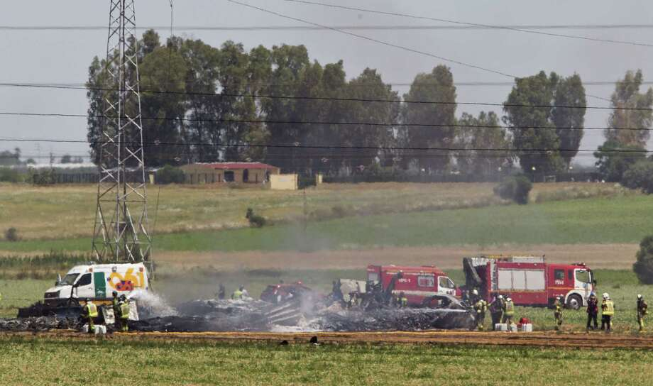 Emergency services personnel work in the area after a plane crash near the Seville airport, in Spain on May 9, 2015. A military transport plane crashed near southwestern Seville airport Saturday, killing its crew, Spain's prime minister said. Photo: AP Photo/Miguel Angel Morenatti  / AP