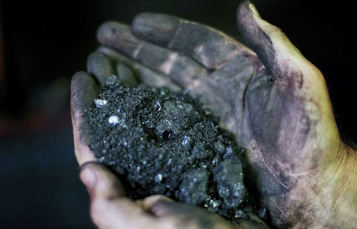 Superintendent Jackie Ratliff, a coal miner of 25 years, holds coal running through a processing plant in Welch, W.Va.